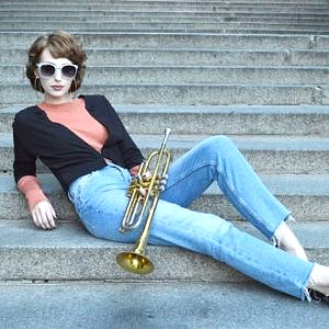Model is lying on the stairs wearing light blue jeans, black bolero, orange turtle neck pullover and sunglasses with blue rim. She is holding golden trumpet
