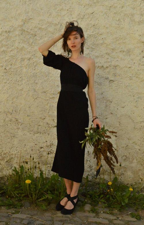 Model is wearing reversible black midi dress with one sleeve