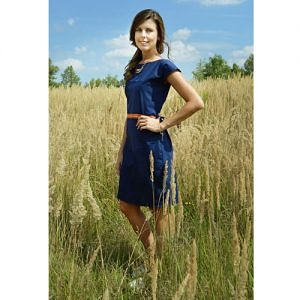 The model is wearing knee lenght blue dress with short sleeves and orange indian motive placed on the waistline