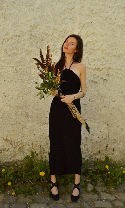 Modelká má oblečené čierne polodlhé šaty s viazaním za krkom