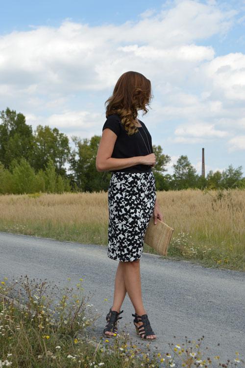 Žena má na sebe úzku sukňu s vysokým pásom po kolená. Sukňa má čiernobiely kvetovaný vzor