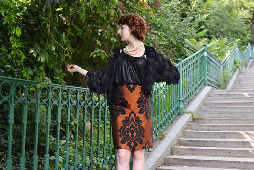 Woman standing on the stairs is wearing orange high waisted pencil skirt with baroque pattern and black vintage style top