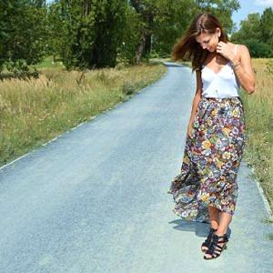 Modelka má oblečenú dlhú farebnú kvetovanú boho sukňu, ktorá je vpredu krátka a vzadu dlhá.