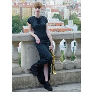 Modelka stojí pri starom kamennom zábradlí, za ňou je výhľad na Prahu. Na sebe má dlhé čierne šaty a v ruke drží zlatú trúbku