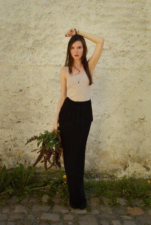 Model is wearing reversible long black skirt