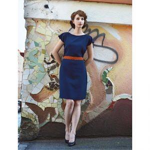 Modelka stojím pred farebným múrom a má na sebe modré šaty po kolená s krátkymi rukávmi a lodičkovým výstrihom.