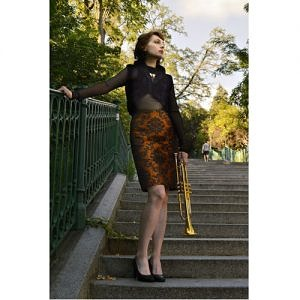 Woman standing on the stairs, holding golden trumpet, is wearing narrow orange skirt owith barogue motive and black vintage style top