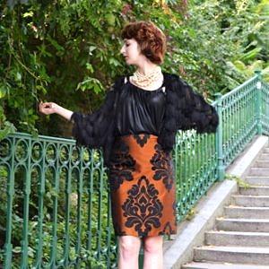 Žena stojaca na schodoch má na sebe recyklovanú elegantnú sukňu so zaujímavým čiernym ornamentom z obdobia baroko