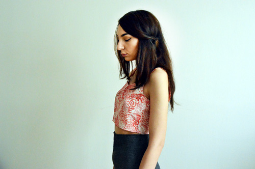 Girl is wearing short sleeveless top with red and white flowers recycled from an old dress
