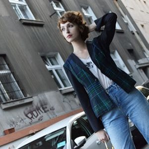 Woman standing in front of a building is wearing tartan jacket with green and blue stripes, black sleeves, pale blue jeans and white top
