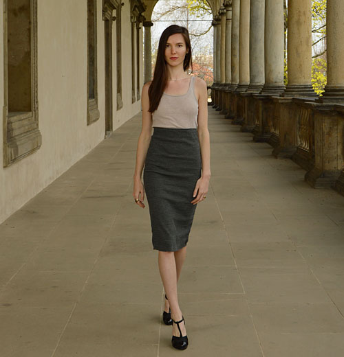 The woman is wearing grey knee lenght skirt with high waist