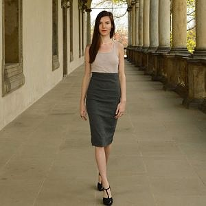 Modelka má oblečenú úzku sivú sukňu pod kolená s veľmi zvýšeným pásom a tielko krémovej farby