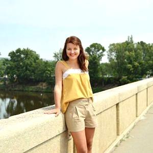 Modelka má oblečené voľné žlté boho tielko s bielou čipkou v predu a so širokými ramienkami.