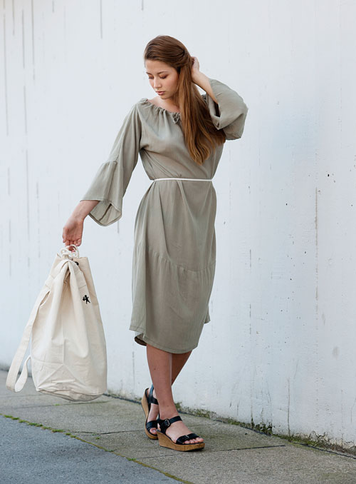 Model is wearing reversible pale green midi dress with long sleeves