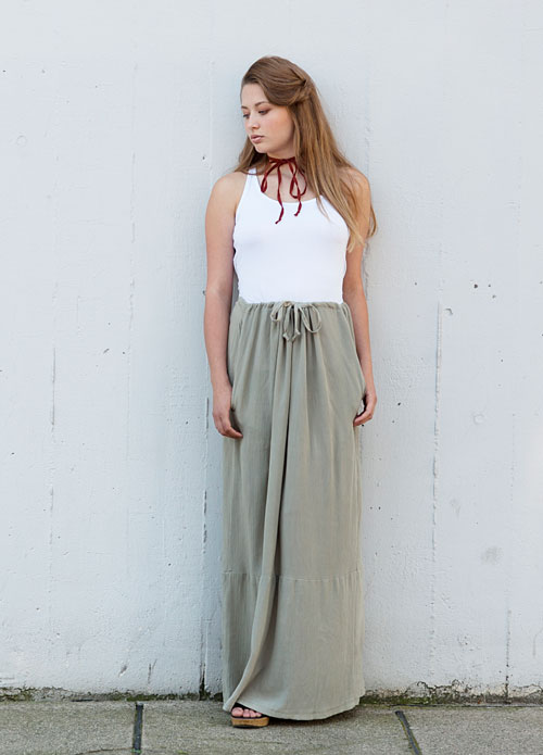 Model is wearing reversible long pale green skirt with pockets