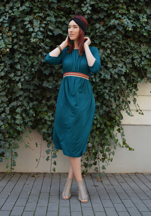 Model is wearing reversible emerald midi dress with two sleeves