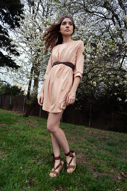 Model is wearing short reversible salmon pink dress with two sleeves