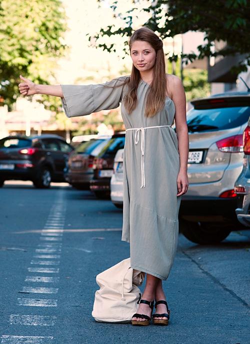Modelka má oblečené svetlozelené pastelové multifunkčné midi šaty bez jedného rukáva
