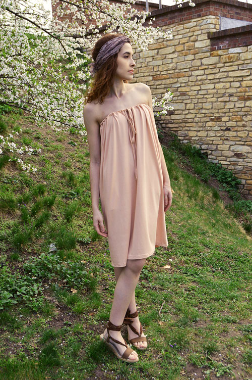 Model is wearing short salmon pink strapless variable dress