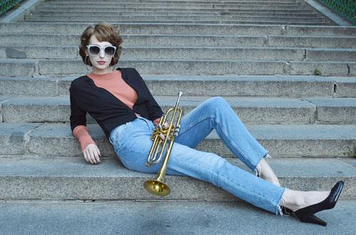 Modelka má na sobě černé bolerko, oranžový rolák a bledě modré džíny