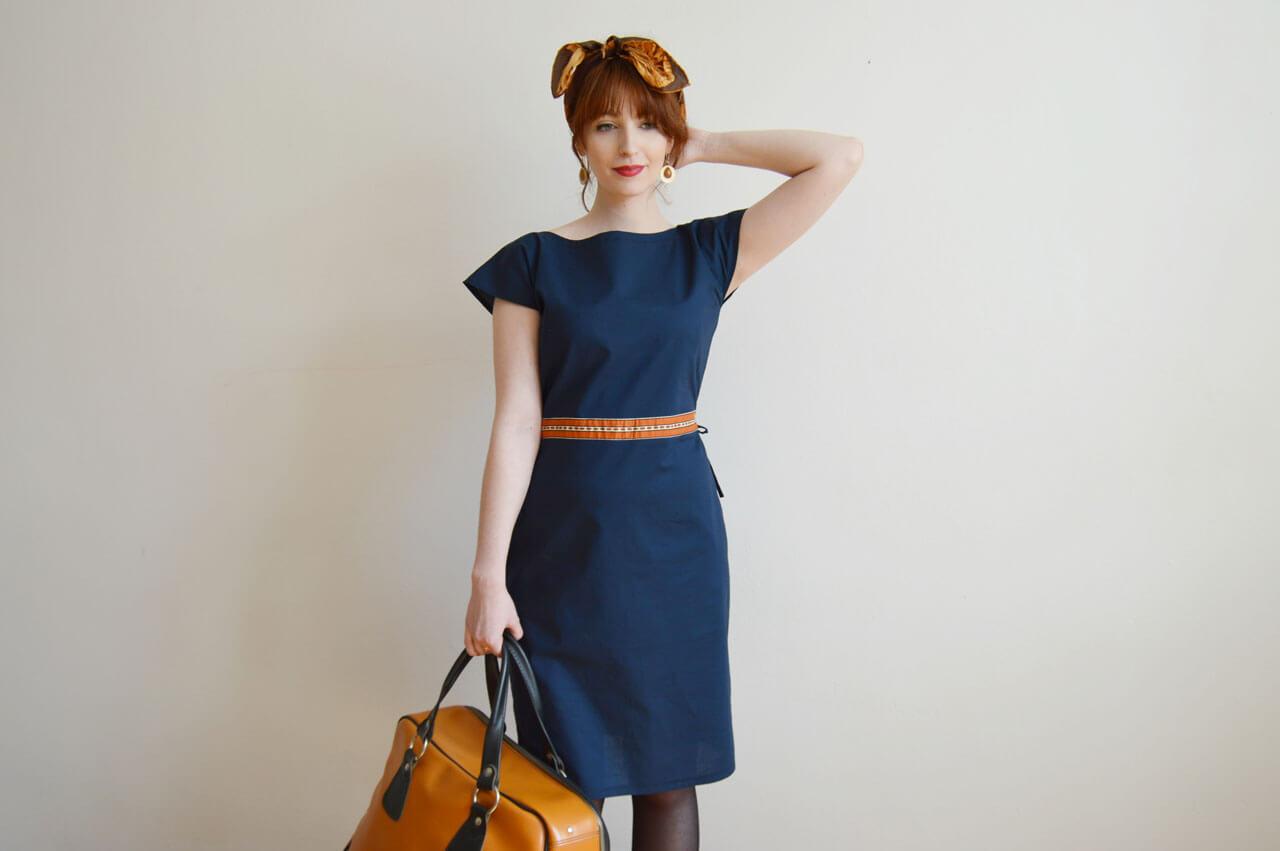 Bavlnené tmavomodré šaty s oranžovým pásikom v páse.