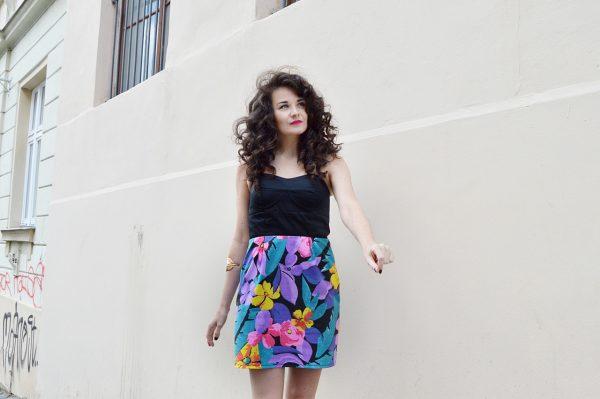 Šaty s čiernym topom bez ramienok a kvetovanou sukňou.