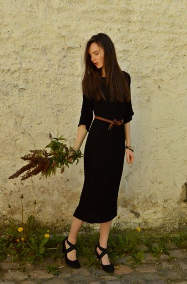 Model is wearing reversible black midi dress with two sleeves