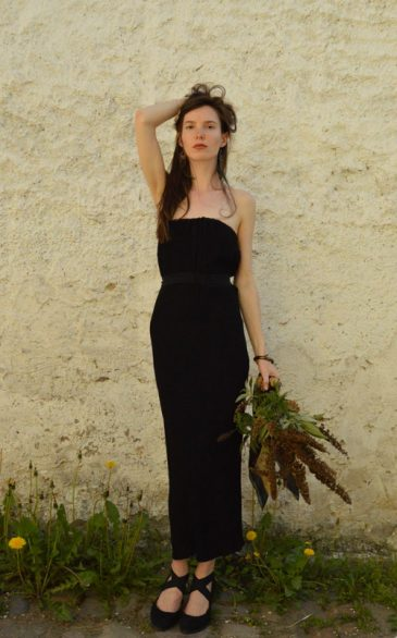 Model is wearing black midi strapless dress