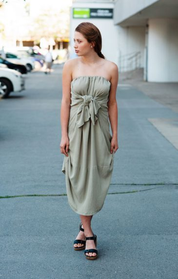 Model is wearing pale green midi strapless dress with bow in front
