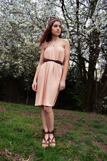 Model is wearing reversible salmon pink short dress tied behind neck