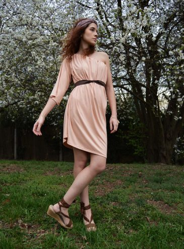 Model is wearing reversible salmon pink short dress with one sleeve
